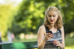 Beautiful  woman typing on smartphone while sitting outdoors. Stock Images