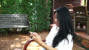 Beautiful woman typing something on her smartphone in garden stock video footage