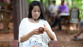 Beautiful woman typing something on her smartphone in garden stock footage