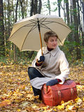 Beautiful woman with umbrella. Resting on a leather chest in the forest royalty free stock photo