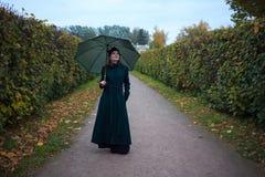 Beautiful woman with umbrella in autumn park. Beautiful vintage style woman with umbrella in autumn park Stock Image