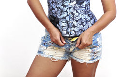 Beautiful woman unbuttoning denim shorts Royalty Free Stock Photography