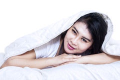 Beautiful woman under blanket in bed stock image