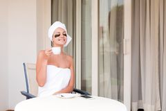 Beautiful woman in under eye patches with cup of coffee and towel on her head. Happy female on vacation enjoying fresh air in. Hotel terrace resort royalty free stock photos