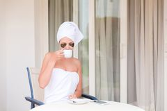 Beautiful woman in under eye patches with cup of coffee and towel on her head. Happy female on vacation enjoying fresh air in. Hotel terrace resort stock photos