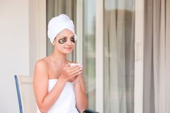 Beautiful woman in under eye patches with cup of coffee and towel on her head. Happy female on vacation enjoying fresh air in. Hotel terrace resort royalty free stock photo