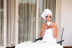Beautiful woman in under eye patches with cup of coffee and towel on her head. Happy female on vacation enjoying fresh air in. Hotel terrace resort stock image