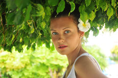 Beautiful woman undger green leafs Stock Photography
