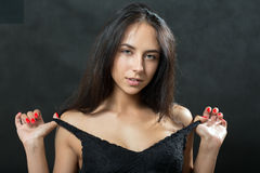Beautiful woman undressing. Beautiful young woman undressing on black background Stock Photography