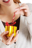 Beautiful woman unwrapping small present. Beautiful woman unwrapping small present held in her hands Stock Images