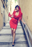 Beautiful woman in urban background. Vintage style. Portrait of a pretty woman, vintage style, in urban background, wearing a red dress Royalty Free Stock Photography