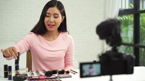 Beautiful woman use brush while review make up tutorial broadcast live video to social network by internet. stock video footage