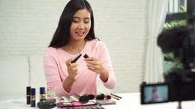 Beautiful woman use brush while review make up tutorial broadcast live video to social network by internet. Beauty blogger present beauty cosmetics while stock video