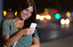Beautiful woman use her phone in the city at night. Stock Photography