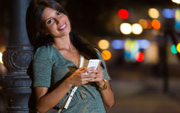 Beautiful woman use her phone in the city at night. Stock Image