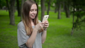 Beautiful woman uses cell smartphone outdoors in the park  - detail. Young attractive happy girl stock footage