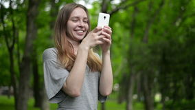 Beautiful woman uses cell smartphone outdoors in the park  - detail. Young attractive happy girl stock video footage