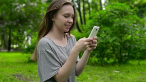 Beautiful woman uses cell smartphone outdoors in the park  - detail. Young attractive happy girl stock video