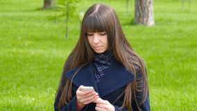 Beautiful woman uses cell smartphone outdoors in the park  - detail . Young attractive happy girl relaxes in a city par stock video