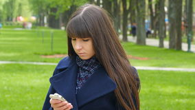 Beautiful woman uses cell smartphone outdoors in the park  - detail . Young attractive happy girl relaxes in a city park stock footage