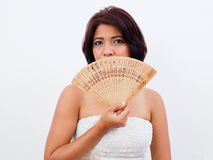 Beautiful woman uses hand fan. Sexy woman hides her face behind a hand fan Royalty Free Stock Images