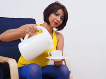 Beautiful woman uses kettle to pour water Stock Photo