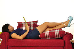 Beautiful woman uses tablet on red sofa Stock Images