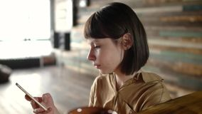 Beautiful woman using app on smartphone in cafe stock footage