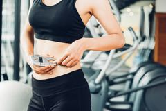 Beautiful woman using caliper fat measure after exercise workout stock photo