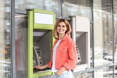 Beautiful woman using cash machine for money withdrawal stock photography