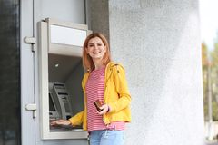 Beautiful woman using cash machine for money withdrawal outdoors stock images