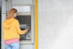 Beautiful woman using cash machine. Space for text royalty free stock image