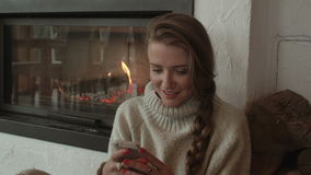 Beautiful woman using a cellphone at home at the warmth of a fireplace. Young woman using smartphone at home stock video