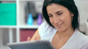 Beautiful woman using a digital tablet, while sitting on the couch at home stock video