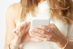 Beautiful woman using electronic smart phone over empty white background. Beautiful woman using electronic smart phone over empty white background Stock Images