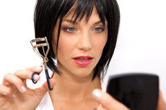 Beautiful woman using an eyelash curler Royalty Free Stock Photography
