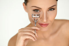 Beautiful Woman Using Eyelash Curler On Curly Long Eyelashes. Eyelash Curler. Portrait Of Beautiful Young Woman Using Beauty Tool On Curly Long Eyelashes Stock Photos