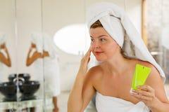 Beautiful woman using facial cream. Young and beautiful woman using facial cream Stock Image