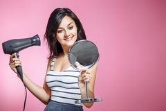 Beautiful woman using a hair dryer and smiling while looking at the mirror on a pink background. royalty free stock image