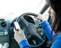 Beautiful woman using her cellphone while driving Stock Image