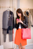 Beautiful woman using her phone while window shopping Royalty Free Stock Photography