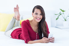 Beautiful woman using her smartphone lying on bed Stock Images