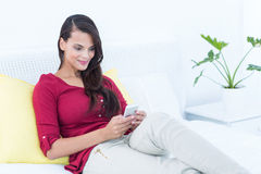 Beautiful woman using her smartphone sitting on bed Stock Photos