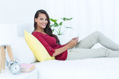 Beautiful woman using her smartphone sitting on bed Royalty Free Stock Photo