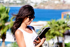 Beautiful woman using her tablet on a sea background Stock Photo
