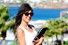 Beautiful woman using her tablet on a sea background Stock Image