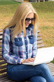 Beautiful woman using laptop on bench in park Royalty Free Stock Photos