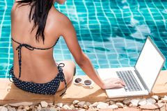 Beautiful Woman using laptop computer on vacation in luxury reso. Rt at Poole blue water Royalty Free Stock Images
