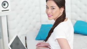 Beautiful woman using a laptop sitting stock video footage
