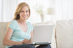 Beautiful Woman Using Laptop On Sofa stock image